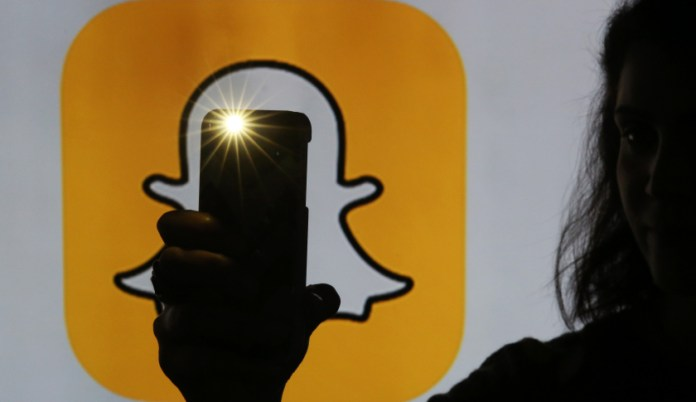 A woman takes a photograph with a camera whilst standing against an illuminated wall bearing Snapchat Inc.'s logo in this arranged photograph in London, U.K., on Tuesday, Jan. 5, 2016. Snapchat Inc. develops mobile communication applications that allows the user to send and receive photos, drawings, text, or videos that will only last for an allotted amount of time. Photographer: Chris Ratcliffe/Bloomberg via Getty Images