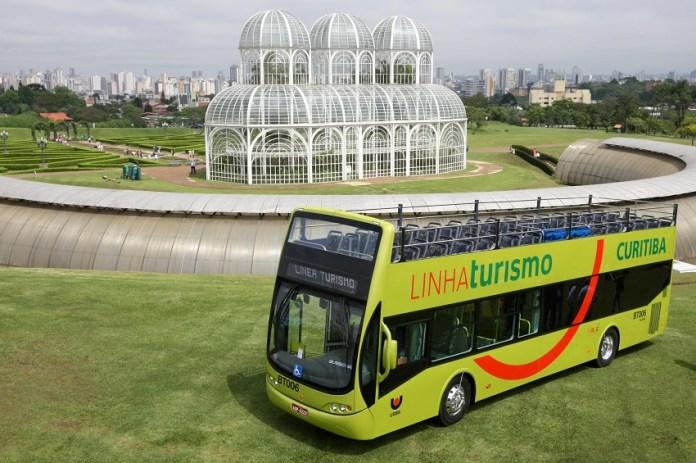 Ônibus de turismo em Curitiba e Jardim Botânico ao fundo