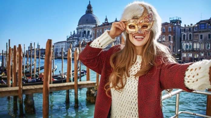 Mulher elegante sorridente, com máscara veneziana em Veneza, Itália.