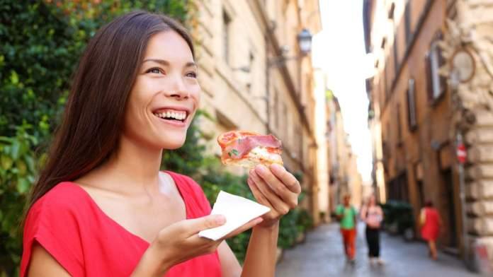 Mulher comendo uma fatia da pizza em Roma, Itália