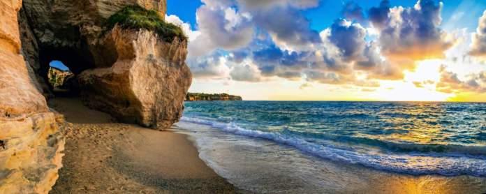 Incrível pôr do sol do mar na pequena praia escondida em Tropea, Calábria, Itália.