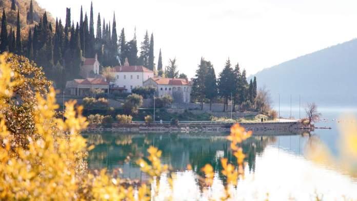 Paisagem de outono. Árvore amarela e alaranjada perto da água azul. Antigo mosteiro Risan, a Baía de Kotor, Montenegro.