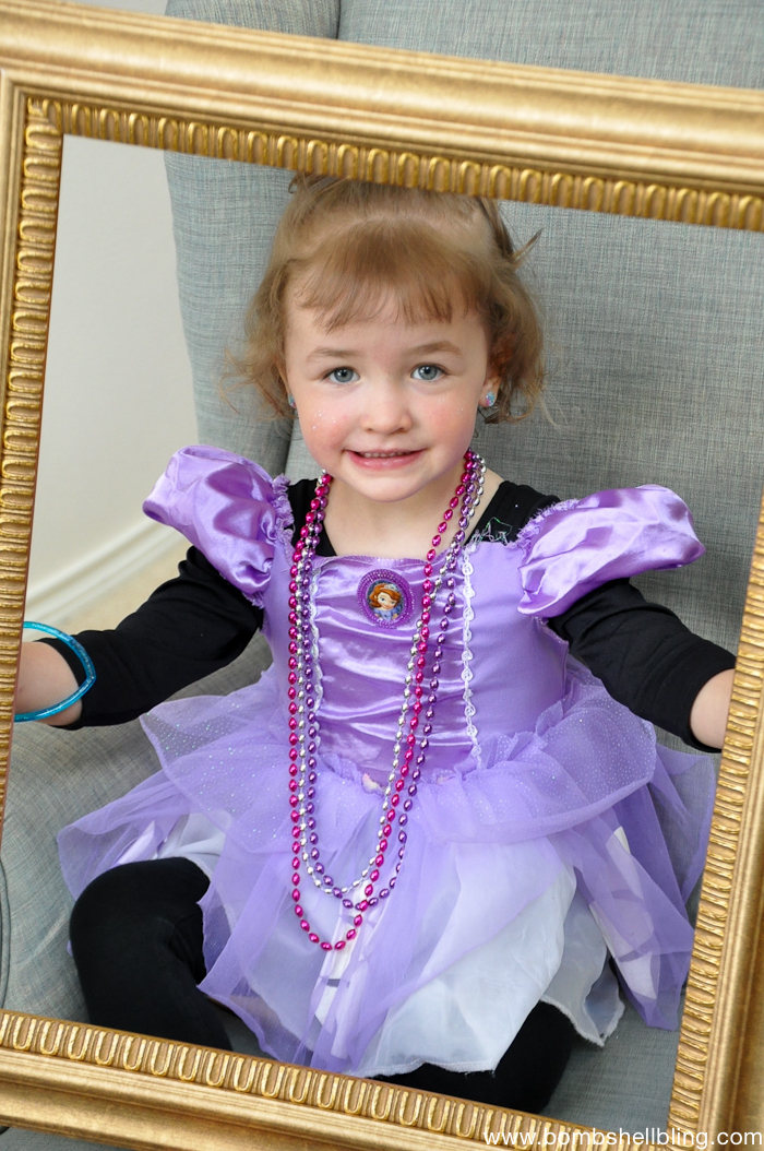 Blonde girl in purple dress holding gold frame at Bippity Boppity Boutique Party