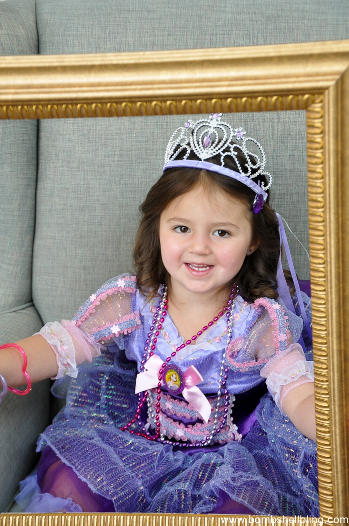 Girl in purple dress holding gold frame at Bippity Boppity Boutique Party