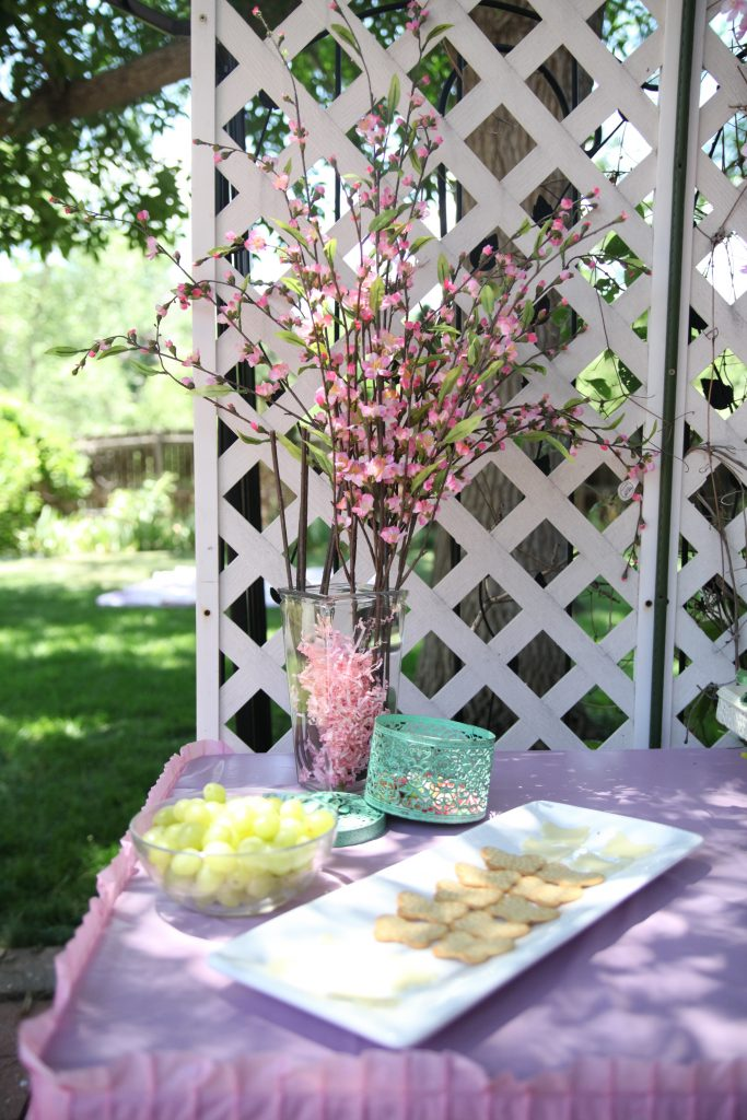 Pink flowers in glass vase on food table at fairy birthday party
