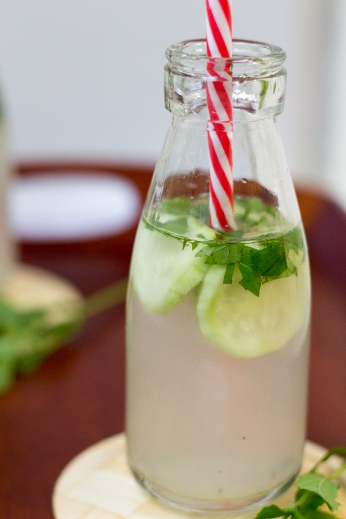 Zoom on one bottle with red straw with lime, mint and cucumber floating.