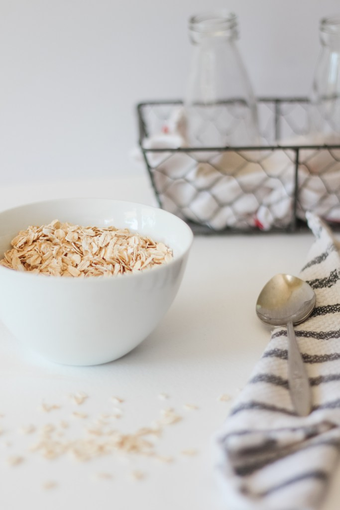 Preparation of homemade oat milk: White bowl with oats with a black and white dishtowel and a mesh basket in the back