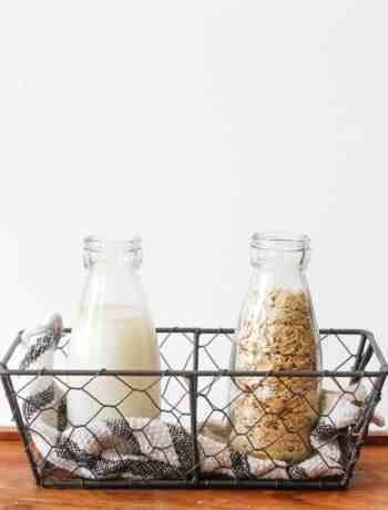 Preparation of homemade oat milk: 2 small bottles in a mesh basket with a black and white dish towel. One bottle is filled with oat milk and one with oats