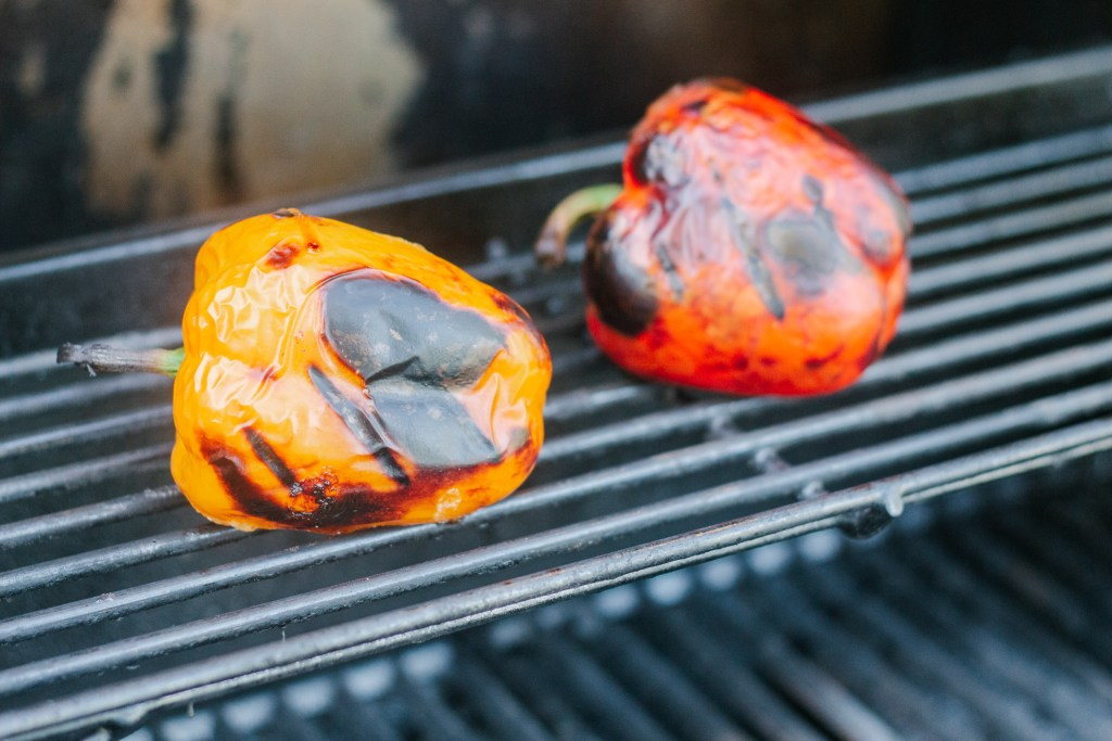 Two peppers roasting on the bbq, one yellow, one red