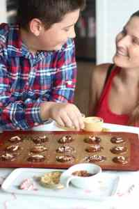 kid and a mom putting toppings on chocolat dis