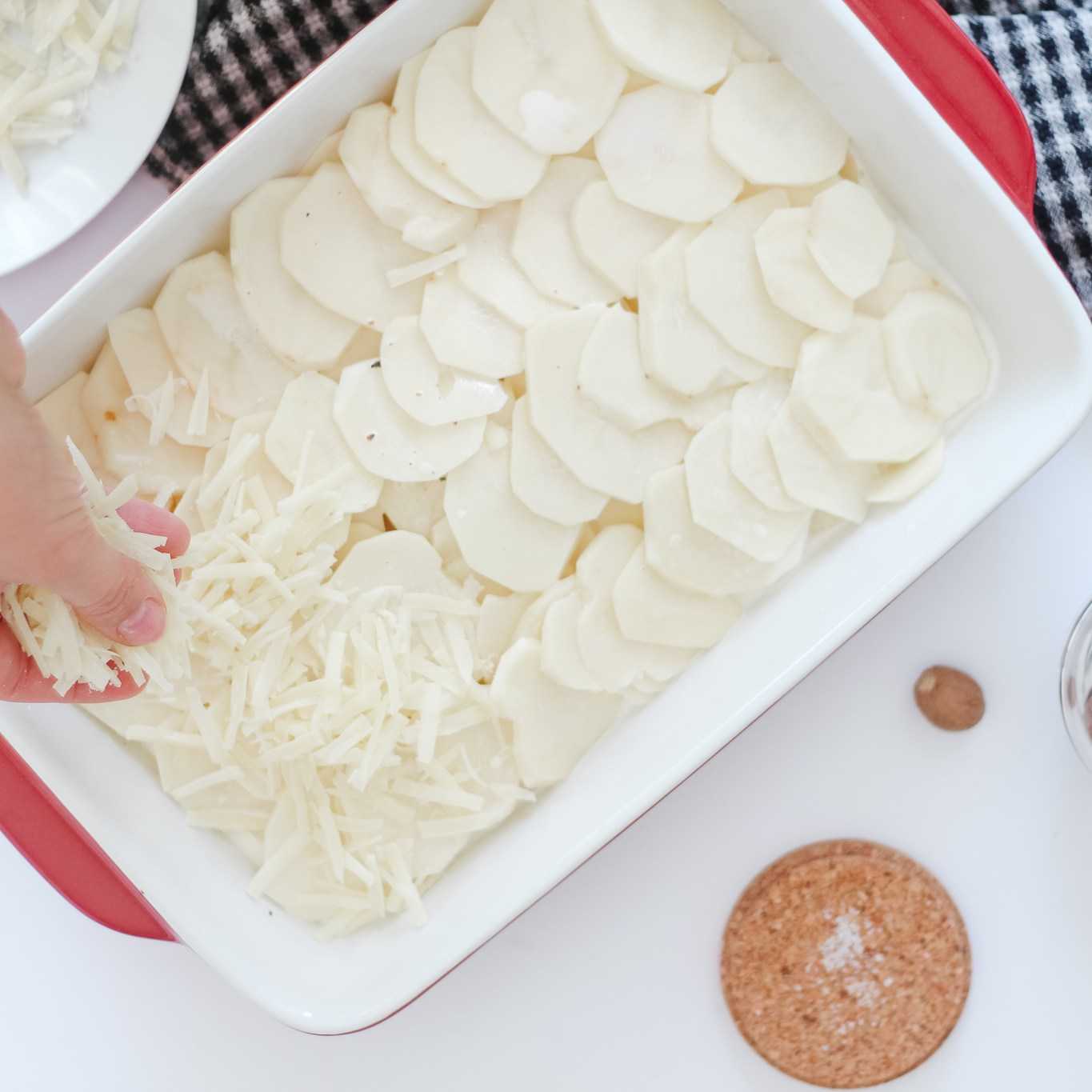 Sprinkling cheese on the sliced potatoes