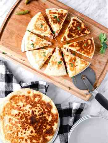 Breakfast quesadillas, one sliced in 8 on a wooden board and another whole
