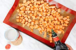 Cubed sweet potatoes spread on a mat, some olive oil is being poured and salt on the side