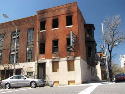 East facade, facing north Calvert Street.  The first floor windows, which contained the smoking lounge and the offices for the National Coalition for Sexual Freedom, are boarded up.  The windows for the dungeon spaces are broken out and open.