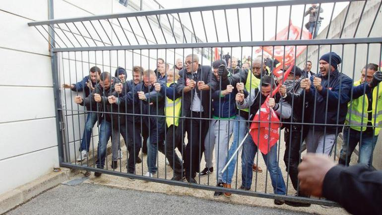 Air France union activists break through a gate as they storm the headquarters to disturb a meeting at Roissy Airport, north of Paris, France, Monday, Oct. 5, 2015. Union activists protesting proposed layoffs at Air France stormed the headquarters during a meeting about the job cuts, zeroing in on two managers who had their shirts torn from their bodies, scaled a fence and fled under police protection. (AP Photo/Jacques Brinon)