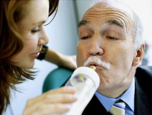 Businessman Being Fed by Baby Bottle Original Filename: 78774650.jpg