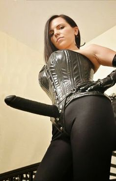 commanding woman in black corset with big strap on dildo