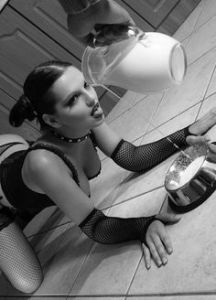 Black and white photo of woman on floor drinking milk from pet bowl