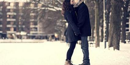 Photo of a couple in the snow in winter cuddling outside