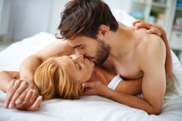 Couple in bed with man on top kissing woman