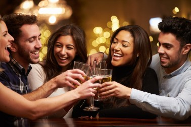 Group of couples laughing and clinking glasses