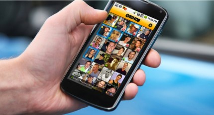Man holding phone with Grindr screen open