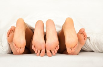 Three pairs of feet in bed