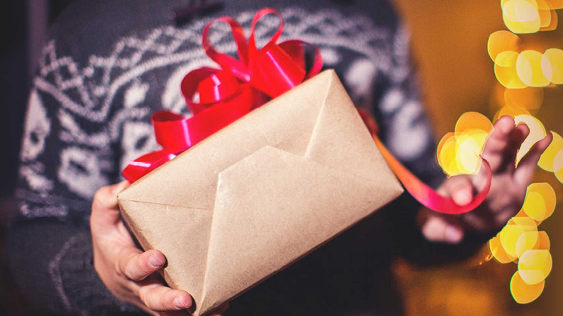a man carries a gift wrapped with ribbon during the holidays