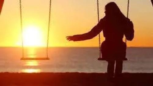 girl sitting alone on swings