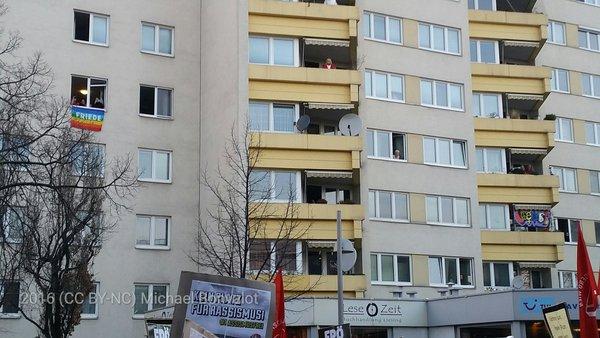 BewohnerInnen winken von oben der Demo #liesingfüralle zu.