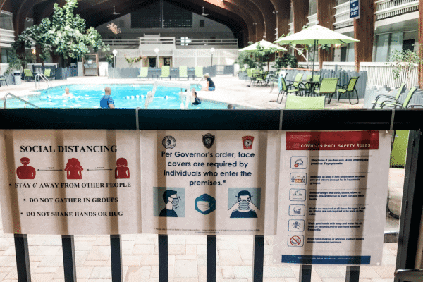 travel-in-2020-masks-at-hotels-near-pool-sign
