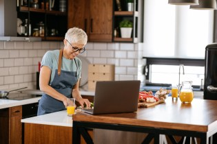 Mature woman following an online recipe on her laptop while cooking