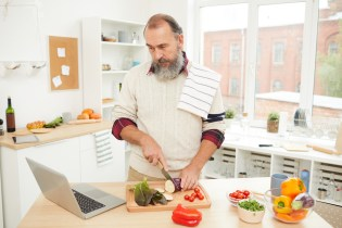 Waist up portrait of bearded senior man watching video recipe via laptop while cooking vegetables in kitchen, copy space