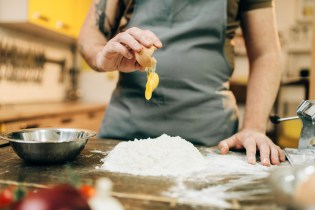 Homemade pasta cooking process, dough preparation. Male chef hands with egg, a bunch of flour on wooden table
