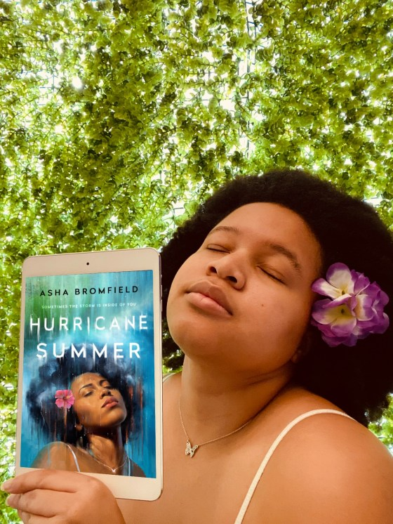 Picture of Alexia with a purple flower in her afro and holding up an ipad with the cover of Hurricane Summer on it