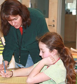 Melissa Stewart working with a student during a school visit