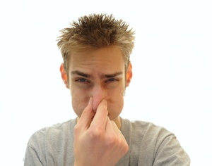 Man plugging his nose from odor