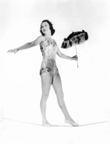 Black and white vintage photo of female circus performer on tight rope