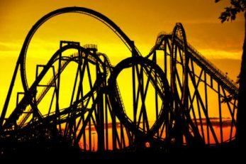 Outline of a roller coaster against a golden sunset.