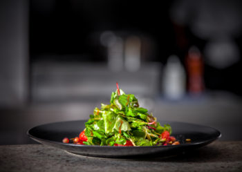 Color picture of a tossed green salad against a black and white background