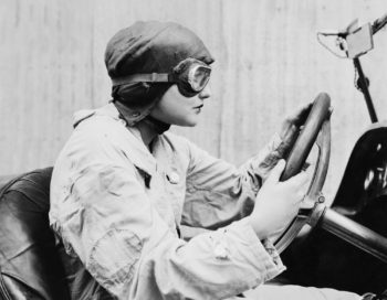 Vintage black and white photo of a female driving open air car wearing an aviator mask and hat on her way to a continuing care retirement community.