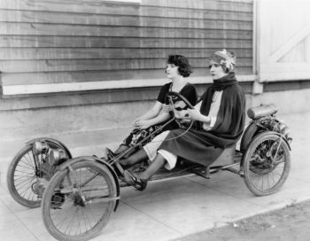 Vintage photo of two women on a four-wheeled bicycle touring a continuing care retirement community.