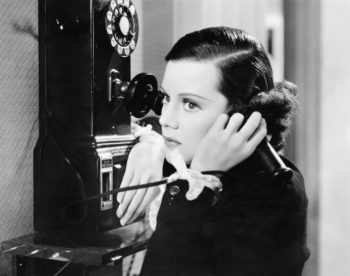 Vintage black and white photo of woman talking on a pay phone