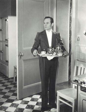 Butler with serving tray standing in doorway looking into room, ready to explain the Trinity Study.