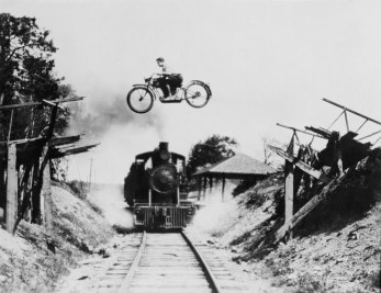 Vintage b/w photo of motor bike jumping a train