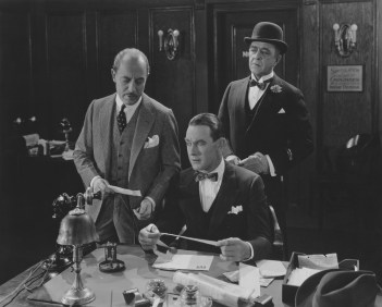Retro black and white photo of man at desk looking regretful he didn't plan to make his money last sooner as two business associates look on.