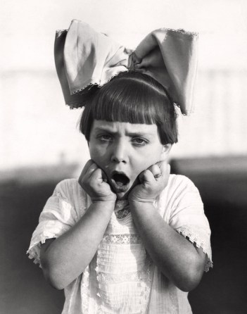 Retro black and white photo of female child with huge bow in hair angrily clutching at her cheeks as she realizes she won't have an inheritance from her parents immediate and longevity annuities.