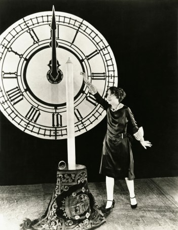 Woman standing by giant clock wondering when the payout for her immediate annuity begins.