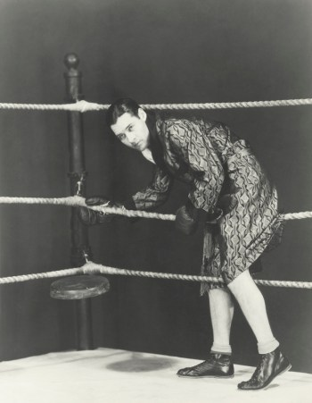 Black and white retro photo of boxer stepping in the ring.