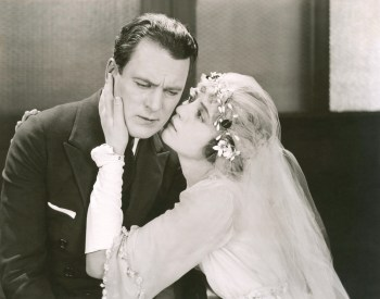 Black and white retro photo of bride whispering ominously to groom.